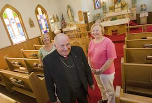 Rev. Joseph Krusienski, pastor of Holy Trinity Polish National Catholic Church, stands with long-time parish members Arlene Strazzulla, left, of Southington, and Marilyn Folcik, right, of Bristol, Thursday, July 24, 2014. The church, located on Summer St. in Southington, is celebrating its 100th year anniversary. | Dave Zajac / Record-Journal